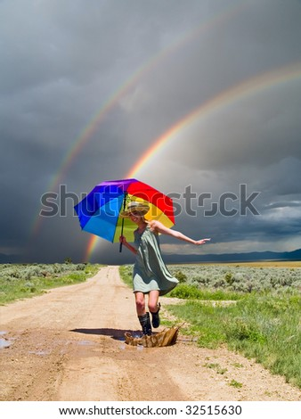 Girl splashing water in a puddle after a rain
