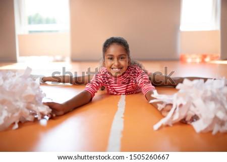 Girl splitting legs. Little beaming dark-skinned cheerleader feeling happy while splitting legs
