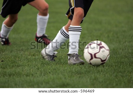 Girl sprints past competitor during a soccer game with ball.