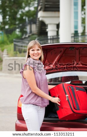 girl stacks a suitcase in a car luggage carrier