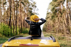 Girl Standing at Car Sunroof Enjoying Road Trip. Woman in Leather Jacket on Summer Getaway. Back View of Beauty Making Selfie Leaning out Yellow Auto Roof with Forest on Background