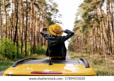 Girl Standing at Car Sunroof Enjoying Road Trip. Woman in Leather Jacket on Summer Getaway. Back View of Beauty Making Selfie Leaning out Yellow Auto Roof with Forest on Background Foto stock ©