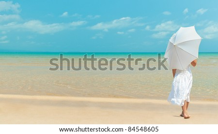 girl standing back on the beach  in white dress with umbrella
