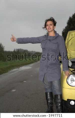 Girl standing by the side of the road with the hood of her car open signaling problems with the car