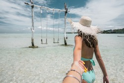 Girl standing in water and looking at swing on sandy beach on paradise Bali island, follow me travel concept