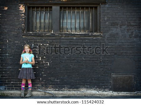 Girl standing next to brick wall holding flowers