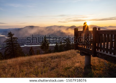 Girl Standing on a Lookout and looking at a Beautiful View of a Canadian City, Kamloops, during a colorful summer sunrise. Located in the Interior British Columbia, Canada. #1507918076