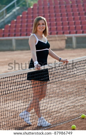 Girl standing on a tennis court for lessons.