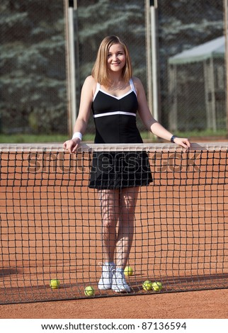 Girl standing on a tennis court for lessons with balls.