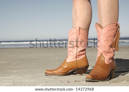 girl standing on beach wearing cowboy boots