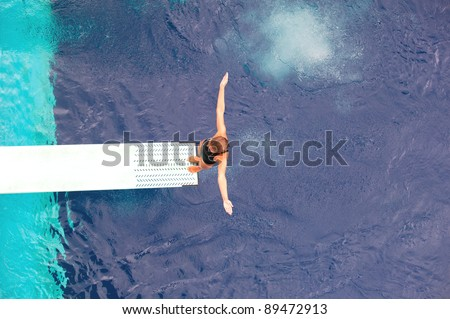 Girl standing on diving board, preparing to dive