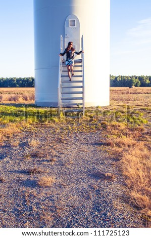Girl standing on entrance to windturbine