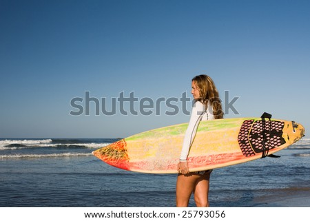 Girl standing on the beach holding a surfboard