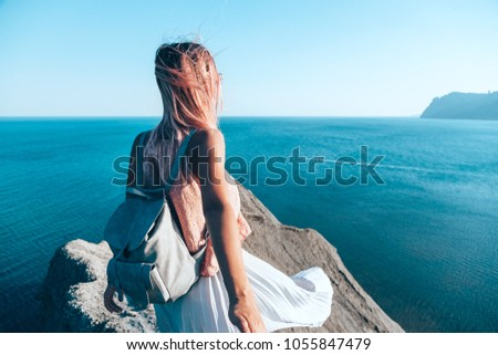 Girl standing on the mountain top over blue sea view. Follow me - POV.
