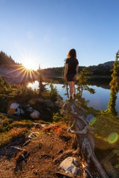 Girl Standing on Tree Stump Looking out over Scenic Lake at Sunset in Canadian Nature. Taken in Whistler, North of Vancouver, British Columbia, Canada.