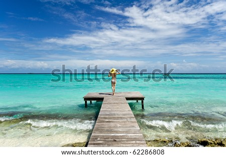 girl standing on wooden bridge extended into the sea
