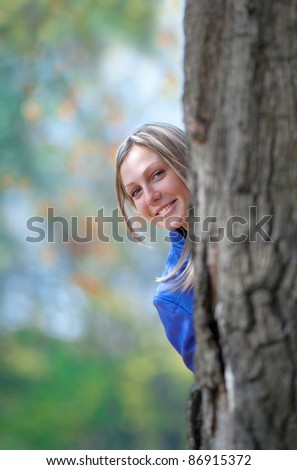 girl stands at the base of a large oak tree