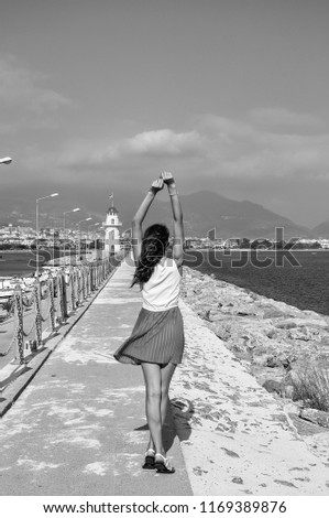 Girl stands back and looks at the lighthouse and the sea, black and white