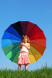 girl stands in meadow with green grass against blue sky and holding colored umbrella