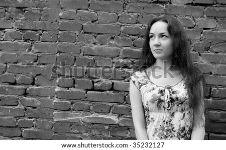 girl stands near the brick wall. black-and-white image