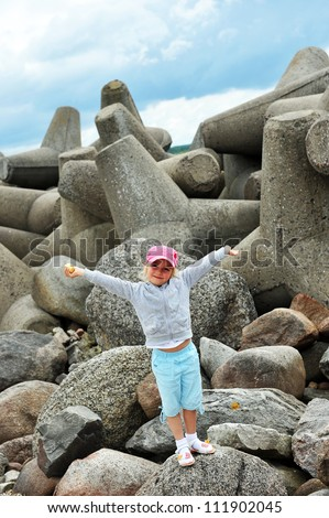 girl stands on  pile of stones. summer vacation on sea