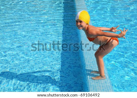 Girl stands on skirting in  pool and prepares to jump in water