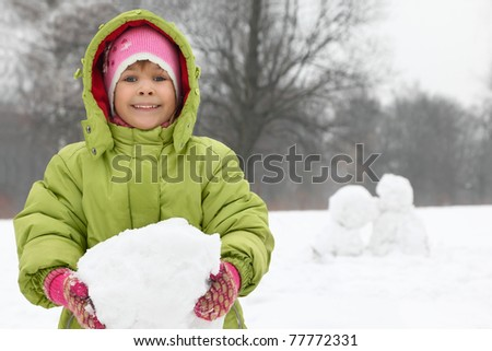 Girl stands on street in winter and have hold of in hands lump of snow