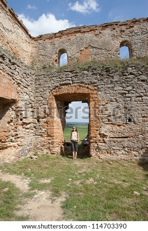 girl stands on the territory of the old fortress