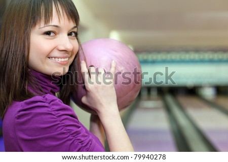 Girl stands sideways and smiles with ball in hands