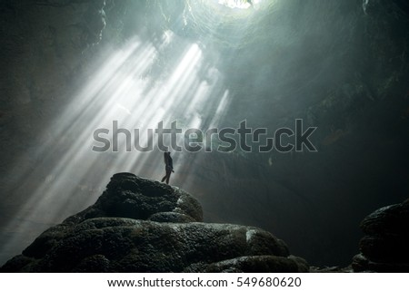 Shutterstock Girl stands under the ray of light in the cave. Jomblang cave. Java, Indonesia