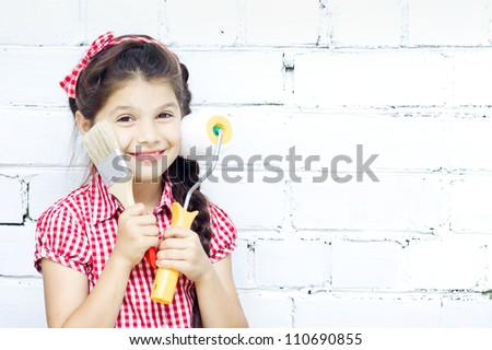 Girl stays with paint brush and roller in hand