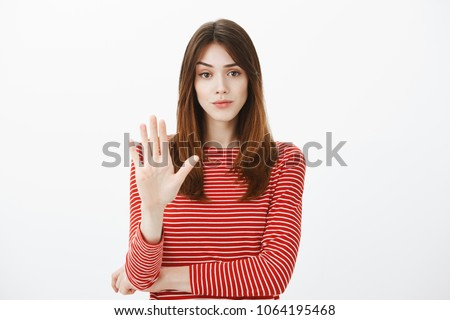 Girl stops friend from drinking alcohol. Studio shot of displeased annoyed attractive caucasian woman, showing palm in enough or no gesture, being disappointed, smirking with dislike over gray wall