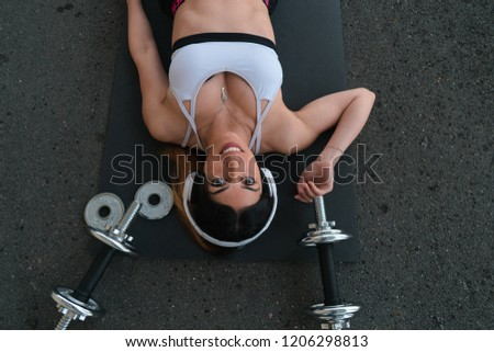 Girl stretches on mat with weights