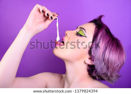 Girl stretches the cud. Sexy girl with short hair. Portrait of a woman with bright colored hair, all shades of purple. Beautiful lips and makeup. . Professional coloring. professional makeup.