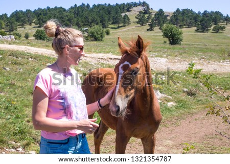 girl strokes a young horse #1321354787