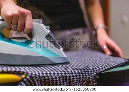Girl strokes clothes with iron