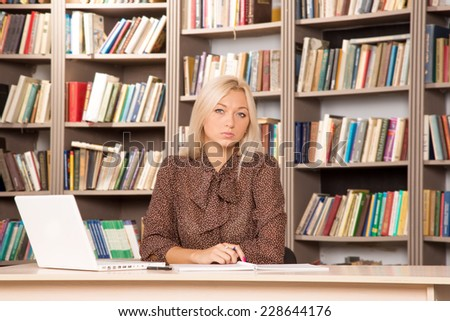 Girl student doing homework in the library. Young modern woman works for his personal laptop computer at table. To get an education at the university. Seriously pursue their studies. Business woman.