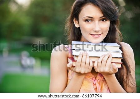 Girl-student holds textbooks, against summer garden.