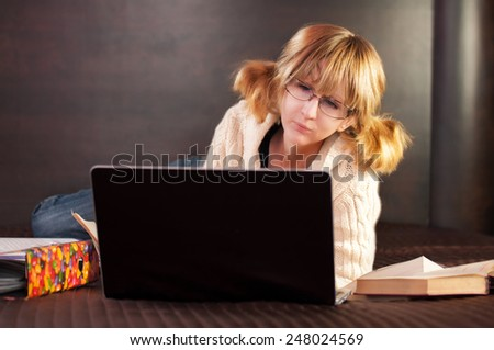girl student preparing for exams in bed. On the bed of the book and a laptop.