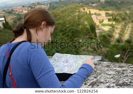 Girl studies tourist map on the stone fence of medieval European city on background of Italian landscape. Italy, Tuscan - stock photo