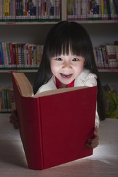 Girl surprised by glowing book