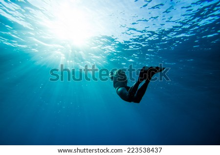 girl swimming underwater with sun rays