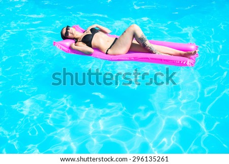Girl swims in the pool on an inflatable mattress