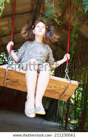 girl swing on wooden board in backyard in summer day