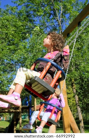 girl swinging on swing happy in trees outdoor up high