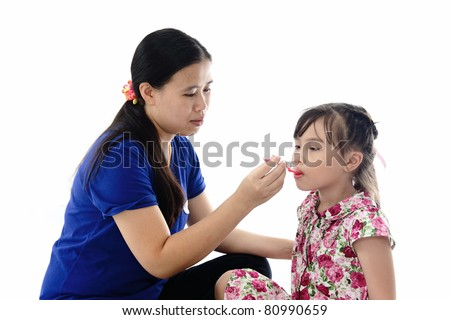Girl takes medicine from mother's hand