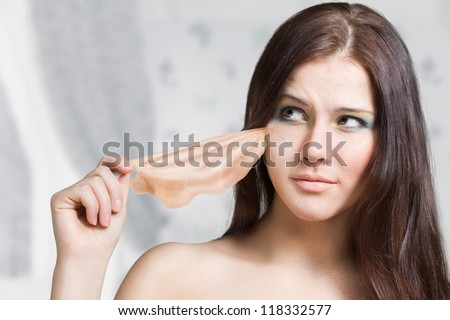 girl takes off the old skin from the face and under her new young