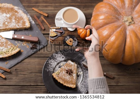 girl takes  picture of  pumpkin pie on  mobile phone on old wooden background