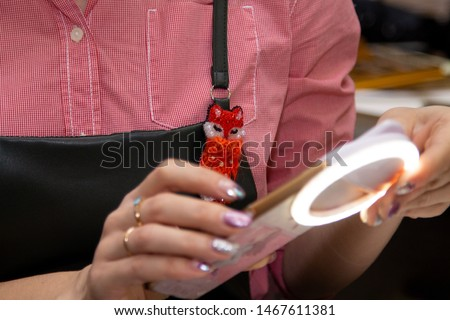 Girl takes picture on the phone with selfie ring, brooch fox, close-up