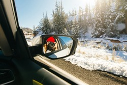 girl takes pictures of herself through a car mirror. car rides through winter forest